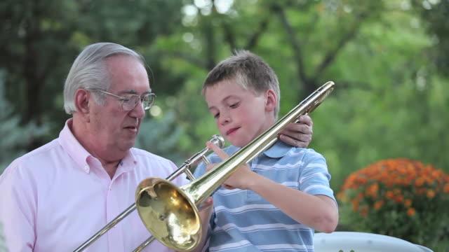 ms pan grandfather teaching grandson (10-11) to play trombone / richmond, virginia, usa - trombone stock videos & royalty-free footage