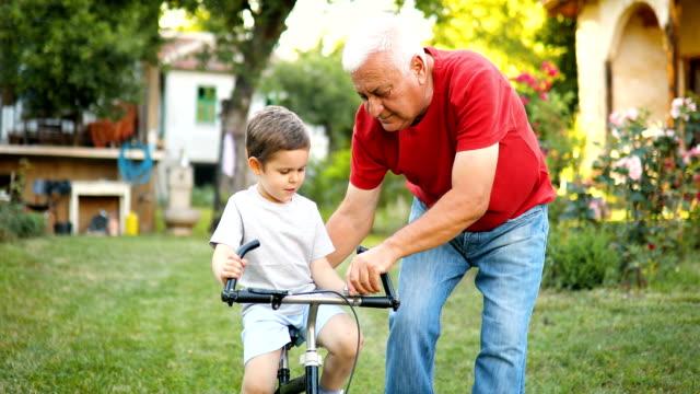 grandfather teaching grandson to ride bike - affettuoso video stock e b–roll