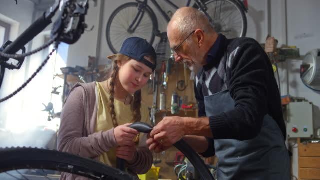 slo mo großvater lehrt seine enkelin, wie man eine fahrradreifenpanne in der werkstatt zu bessern - teenager alter stock-videos und b-roll-filmmaterial