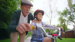 SLO MO Grandfather teaching his son to ride a bike and jumping from excitement when the boy succeeds