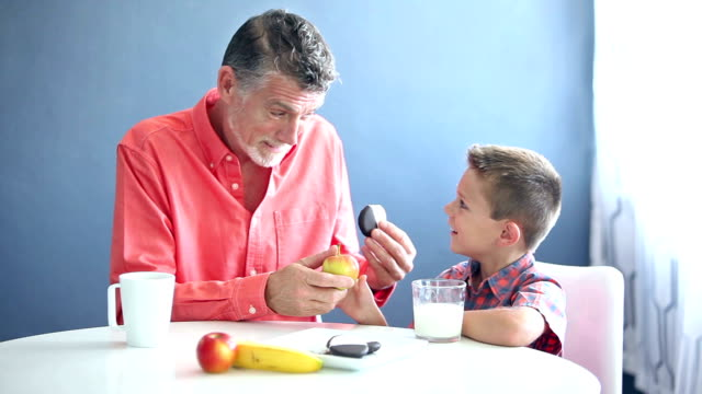 vídeos de stock e filmes b-roll de grandfather teaching little boy to eat healthy food - lanche