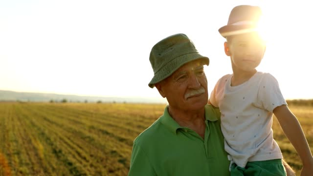 grandfather walking outdoors with grandson - scena rurale video stock e b–roll