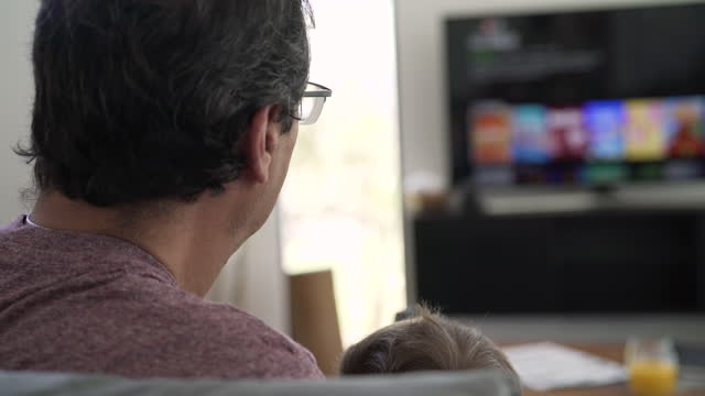 grandfather watching tv at home with grandson - less than 10 seconds stock videos & royalty-free footage