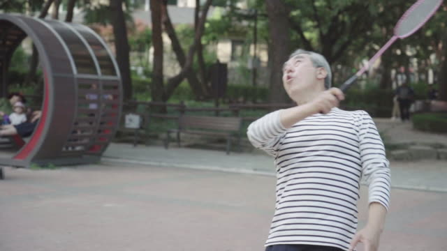 vidéos et rushes de a grandfather who is happy playing badminton at park - badminton sport