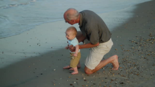 MS Grandfather with baby boy (2-5 months) on beach / Millville, Delaware, USA