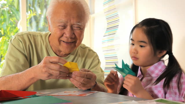 MS Grandfather with granddaughter (8-9) learning to make origami crane / Los Angeles, California, USA