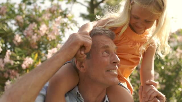 vídeos de stock e filmes b-roll de grandfather with granddaughter on shoulders playing in park. - carregar uma pessoa nos ombros