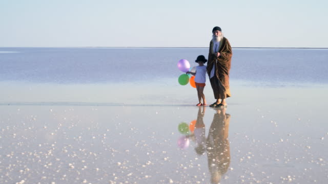 Grandfather with granddaughter playing with colored balloons on the water