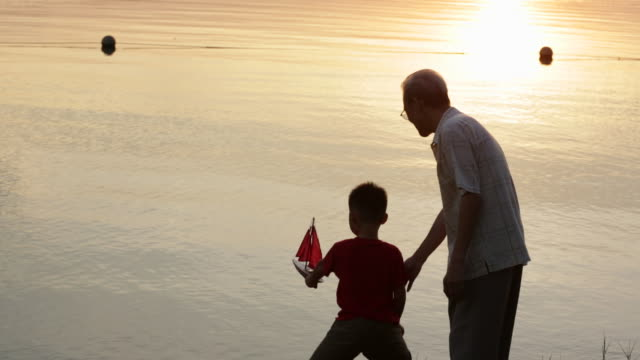 WS Grandfather with grandson getting ready to float a model boat at lake