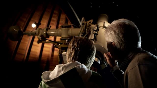 vídeos de stock e filmes b-roll de avô e neto no observatório - explorador