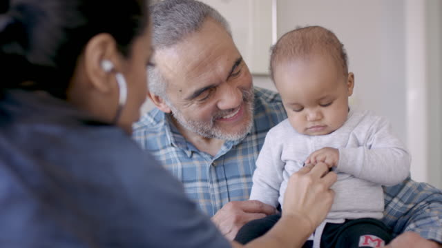 grandfather with his baby grandson at doctors appointment - general practitioner stock videos & royalty-free footage