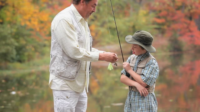 MS TD Grandfather with two prosthetic legs teaching grandson (8-9) how to bait fishing pole / Richmond, Virginia, USA