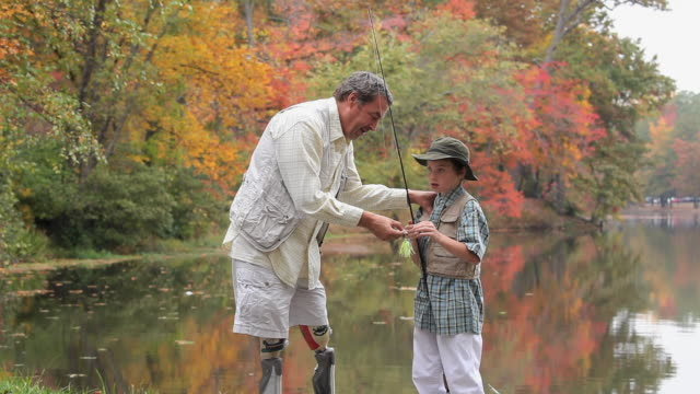 ms td grandfather with two prosthetic legs teaching grandson (8-9) how to bait fishing pole / richmond, virginia, usa - prosthetic equipment stock videos & royalty-free footage