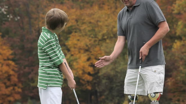 ms td grandfather with two prosthetic legs teaching grandson (8-9) how to play golf / richmond, virginia, usa - artificial limb stock videos & royalty-free footage