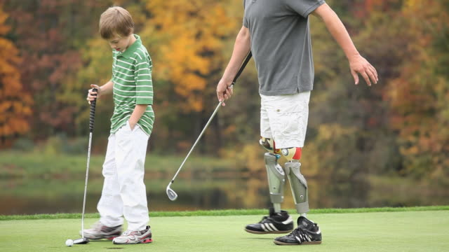 stockvideo's en b-roll-footage met ms pan grandfather with two prosthetic legs teaching grandson (8-9) how to play golf / richmond, virginia, usa - verlamming