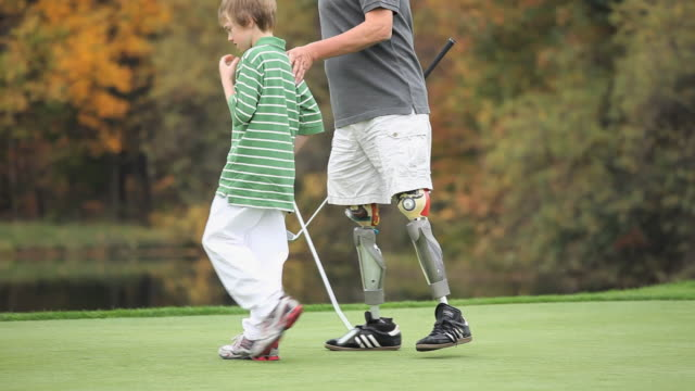 ms pan tu grandfather with two prosthetic legs teaching grandson (8-9) how to play golf / richmond, virginia, usa - golf course stock videos & royalty-free footage