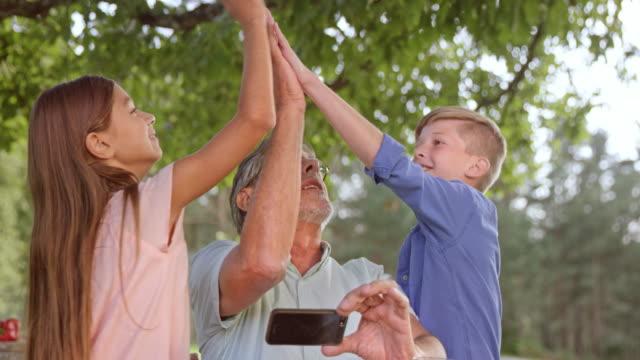 SLO MO barnbarn gör en high five med sin morfar på en picknick