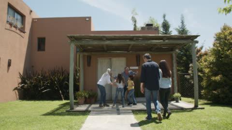 barnbarn med sina föräldrar kör för att krama far-och morföräldrar besöker dem hemma - besök bildbanksvideor och videomaterial från bakom kulisserna
