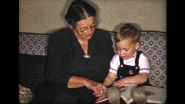vidéos et rushes de 1957 grandma and boy on couch reading book - grand mère
