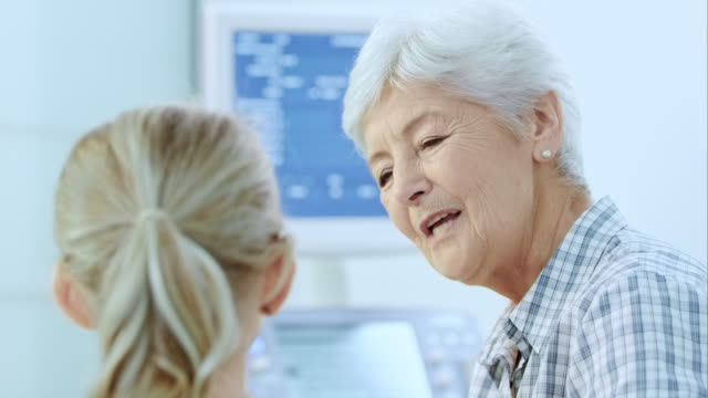 nonna e nipote chiacchierando mentre aspetta esame - accarezzare video stock e b–roll