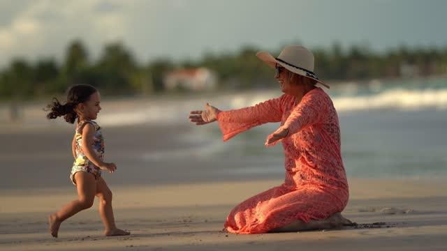 grandma hugging her granddaughter on the beach - grandmother stock videos & royalty-free footage