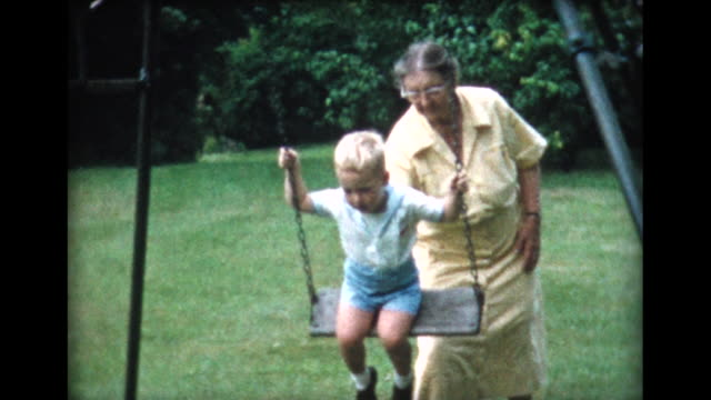 vidéos et rushes de 1958 grandma pushes boy on swing - grand mère
