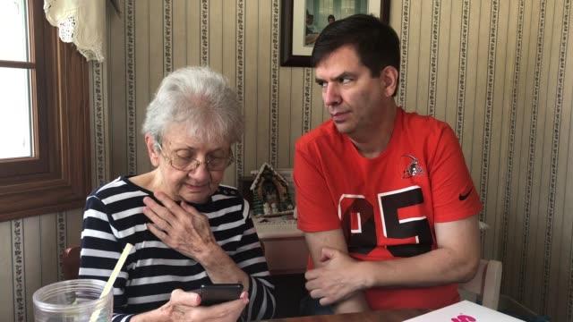 grandma receives smartphone for the very first time - 出来事の発生点の映像素材/bロール