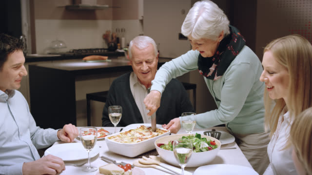 grandma serving lasagna at family dinner - dining stock videos & royalty-free footage