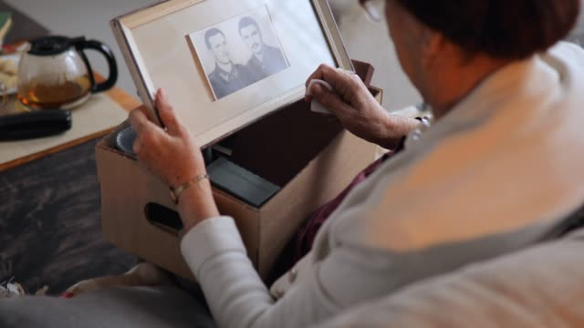 vídeos de stock, filmes e b-roll de avó que senta-se em casa e que olha fotos velhas - imagem