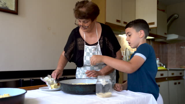 grandma teaching her grandson how to prepare rolls - french food stock videos & royalty-free footage