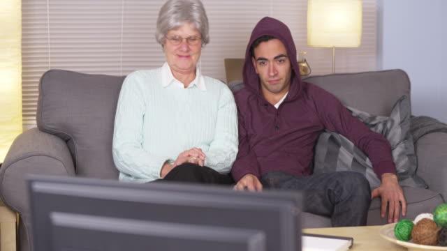 grandma watching tv with bored grandson - プエルトリコ人点の映像素材/bロール