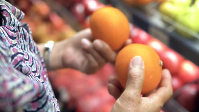 vídeos y material grabado en eventos de stock de grandmom elige frutas y compras en supermercado - dos objetos