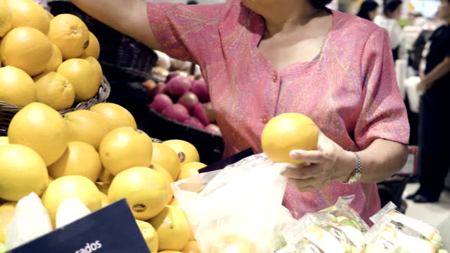 grandmom chooses fruit and shopping in supermarket - due oggetti video stock e b–roll