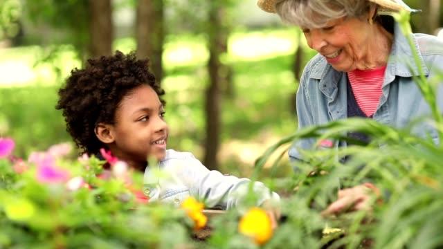 vidéos et rushes de grand-mère et enfant jardiner à l'extérieur au printemps. - parterre de fleurs