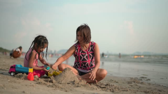 Grandmother and daughter playing in the sand at the beach