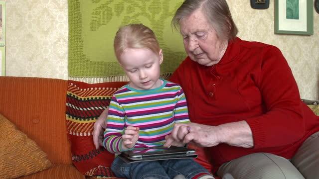 vidéos et rushes de grand-mère et tablette numérique - prendre sur les genoux