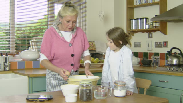 grandmother and grandaughter baking in a country farmhouse kitchen, close up adding sugar. - mixing bowl stock videos and b-roll footage