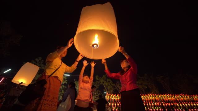 vidéos et rushes de grand-mère et petit-enfant en robe thaïlandaise libérant le ciel lanterne en loi krathong festival chiang mai thaïlande - spirituality