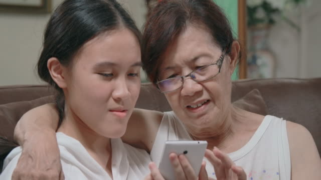 slo mo grandmother and grandchild using smartphone at home - grandmother stock videos & royalty-free footage