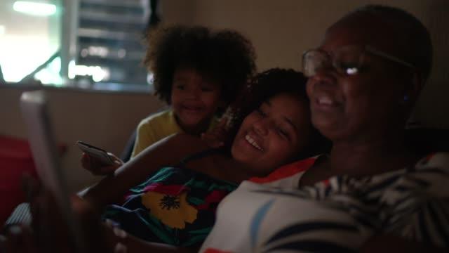 vídeos de stock, filmes e b-roll de avó e netos tendo uma chamada de vídeo em tablet digital em casa - isolado