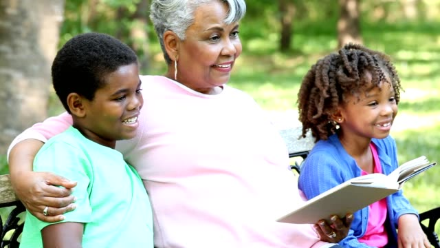 Grandmother and grandchildren reading books and or digital tablet outdoors together.