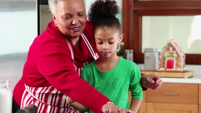 MS TD Grandmother and Granddaughter Baking Gingerbread Men Cookies in Kitchen / Richmond, Virginia, USA