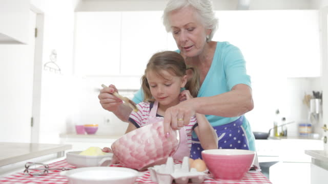 stockvideo's en b-roll-footage met grandmother and granddaughter baking in kitchen - onderwijzen