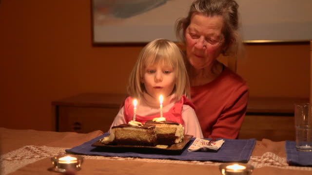 grandmother and granddaughter blow out candles - birthday candles stock videos and b-roll footage
