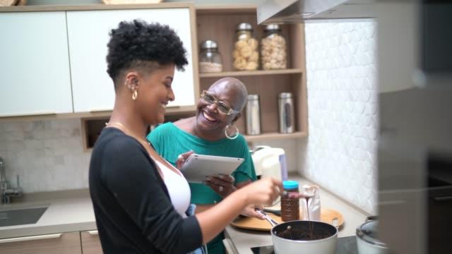 vídeos de stock, filmes e b-roll de avó e neta que cozinham o chocolate em casa - receita