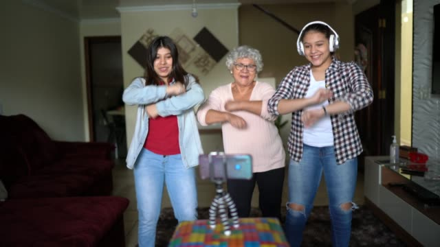 grandmother and granddaughter dancing and recording using mobile to a vlog or social media at home - live broadcast stock videos & royalty-free footage