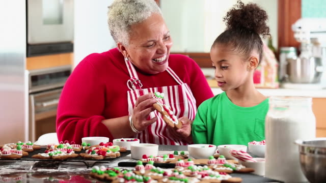 MS Grandmother and Granddaughter Decorating Gingerbread Men Cookies in Kitchen / Richmond, Virginia, USA