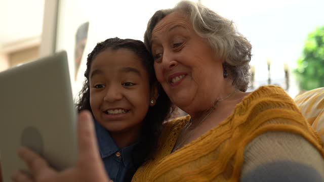 grandmother and granddaughter doing a video call using digital tablet at home - granddaughter stock videos & royalty-free footage