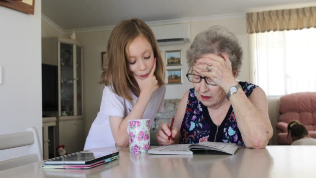 grandmother and granddaughter doing crossword puzzle together - crossword stock videos & royalty-free footage