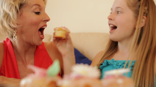 grandmother and granddaughter eating cup cakes together indoors. - dessert stock videos & royalty-free footage